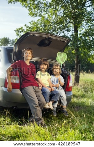 Three cheerful child sitting in the trunk of a car on nature - stock photo