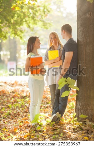 Three cheerful college students standing in a park talking - stock photo
