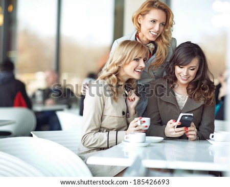 Three cheerful girlfriends enjoying their spare time - stock photo