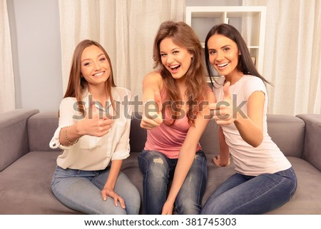 Three cheerful girlfriends sitting on the sofa and show a thumbs up - stock photo