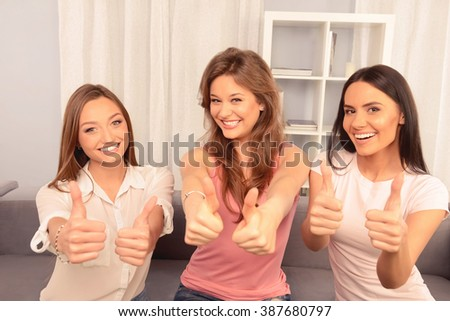 Three cheerful girlfriends sitting on the sofa and showing thumbs up - stock photo