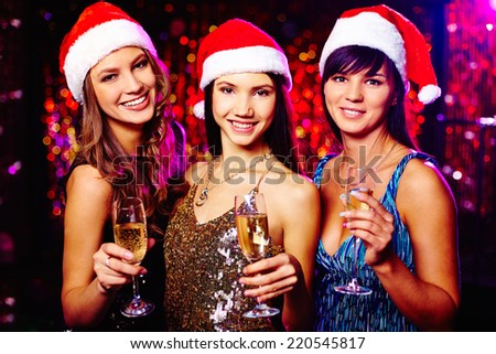 Three cheerful girls in Santa caps wishing you merry Christmas - stock photo
