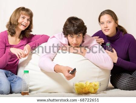 Three cheerful teenage friends watching TV and having snack - stock photo