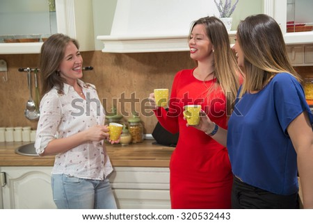 Three cheerful young women having fun and laughing in the kitchen. They are drinking coffee while talking to each other. - stock photo