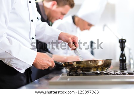 Three chefs - men and woman - in hotel or restaurant kitchen working and cooking in team - stock photo