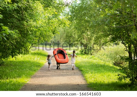 Three children carry a rubber boat with oars on a footpath in the forest - stock photo