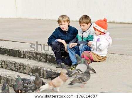 three children feeding doves in the city - stock photo