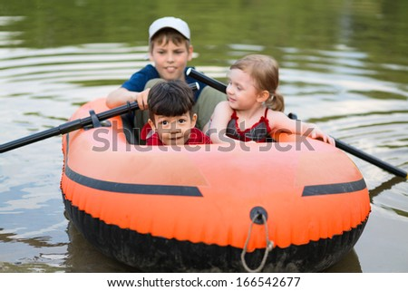 Three children float on a rubber boat with oars, focus on little boy. - stock photo