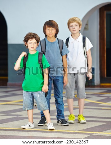 Three children in a row in elementary school on a schoolyard - stock photo