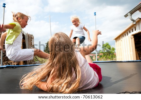 Three children jumping on a trampoline in front of their home - stock photo