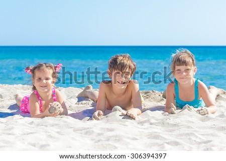 three children, kids, boy and girls, enjoying summer vacation on sand beach - stock photo