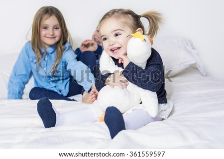 three children, kids, boy and girls, playing  in bed - stock photo