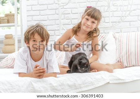 three children, kids, boy and girls, playing with black little cat, kitten, at home, in bed - stock photo