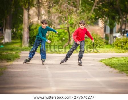 Three children on in line skates in park - stock photo