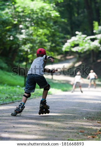 Three children on inline skates in park - stock photo