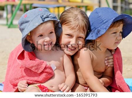 three children on the beach - stock photo
