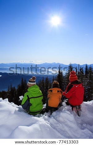 Three children outside, playing in snow on a high mountainside. - stock photo