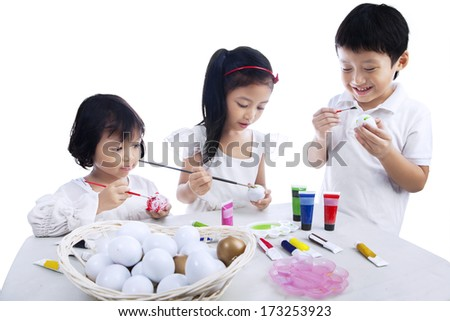 Three children painting Easter eggs isolated on white background - stock photo