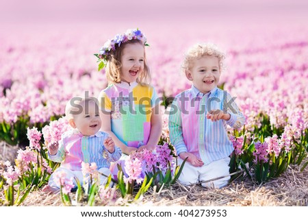 Three children playing in beautiful hyacinth flower field. Little girl, toddler boy and baby play in sunny summer garden with purple flowers. Kids having fun outdoors. Brothers and sister together. - stock photo