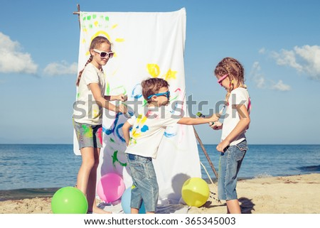 three children playing with paint on the beach at the day time. Concept Brother And Sister Together Forever - stock photo