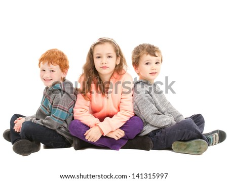 Three children sitting cross legged on floor waiting patiently. On white. - stock photo
