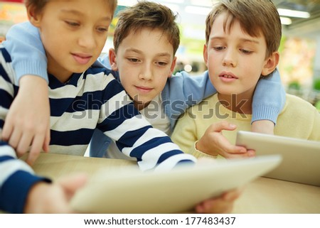 Three children sitting in cafe with touchpads - stock photo