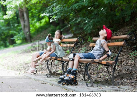 Three children sitting on a park bench after skating - stock photo