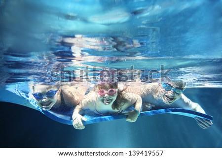 Three children smiling and having fun underwater - stock photo