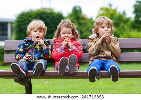 Three children: two little boys and one girl sitting on bench and eating chocolate - stock photo