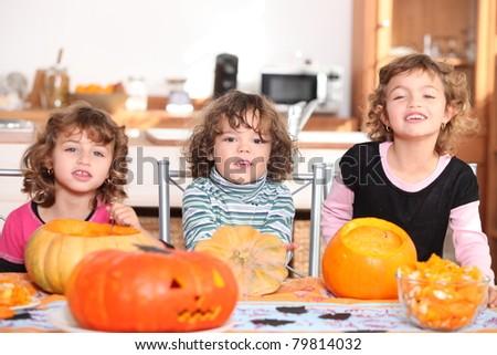 Three children with pumpkins - stock photo