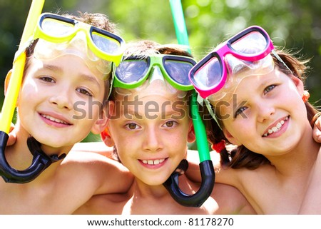 Three children with snorkels looking at camera and smiling - stock photo