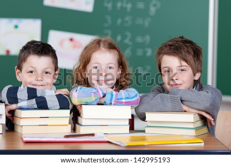 Three children with stack of books inside the classroom - stock photo