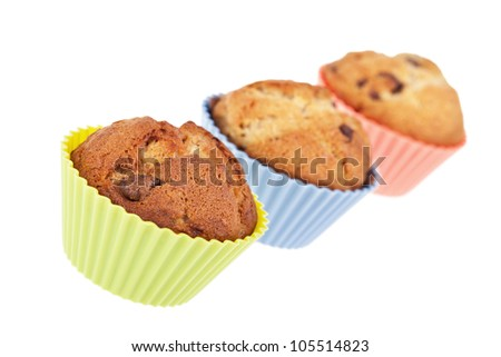 Three chocolate chip banana muffins in bright silicone cases. Intentional shallow Depth of Fie;d. - stock photo