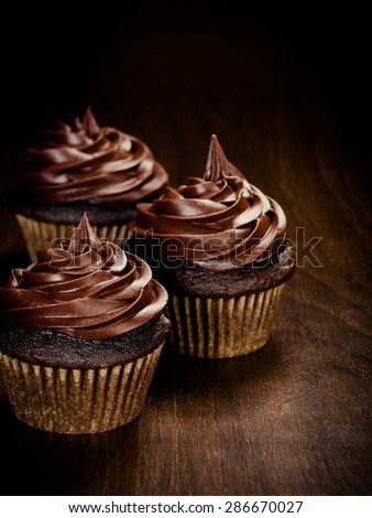 Three chocolate cupcakes over a dark wooden background - stock photo