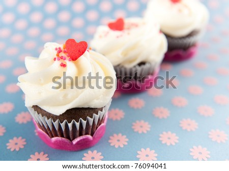 Three Chocolate Cupcakes with Vanilla Icing and Sprinkles - stock photo