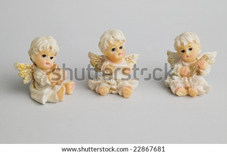 Three Christmas Angels over grey background - stock photo