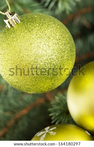Three christmas balls hanging on a green tree.  - stock photo