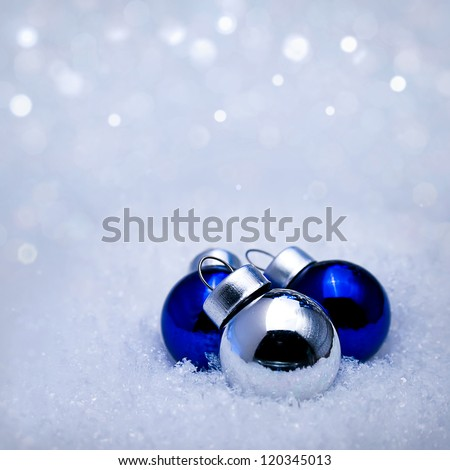 Three Christmas balls of different colors in the snow - stock photo