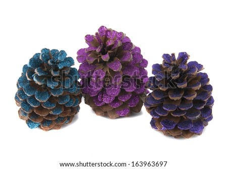 three christmas pinecones painted with colored glitter - stock photo