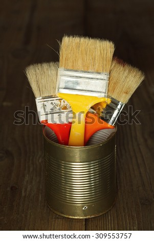 Three clean paint brushes in tin can - stock photo