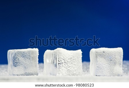 Three clear ice cubes covered with hoarfrost - stock photo