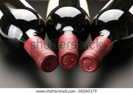 Three closed red wine bottles lying on dark background. - stock photo