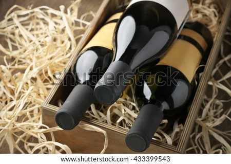 Three closed wine bottles lying on straw in vintage wooden box. - stock photo
