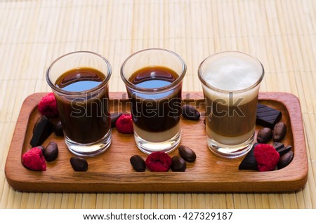 Three coffee cups served on wooden tray with dried raspberries and crushed chocolate.  - stock photo