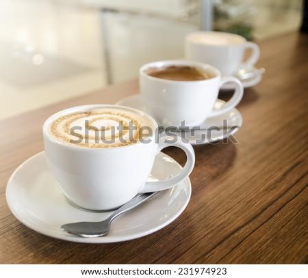 Three coffee cups with cappuccino, caramel macchiato, latte - stock photo