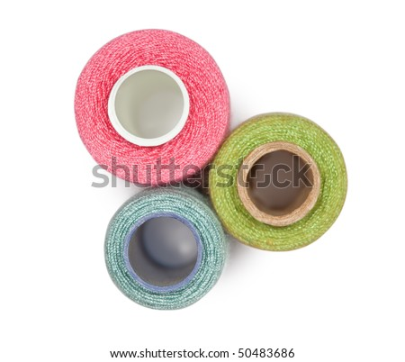 Three coils with multi-coloured sewing threads isolated on white background, top view - stock photo