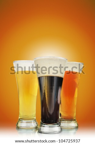Three cold beer glasses have foam and are on a golden background with a highlight to add tour text message. Use it for a Bar or celebration concept. - stock photo