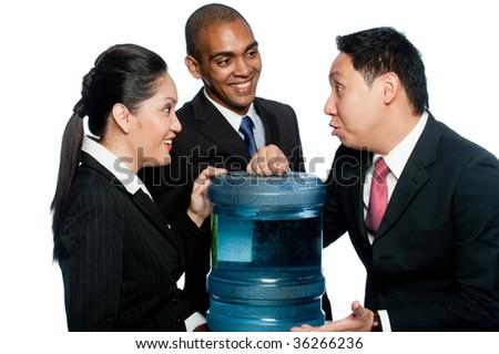 Three colleagues stand around a water cooler gossiping - stock photo