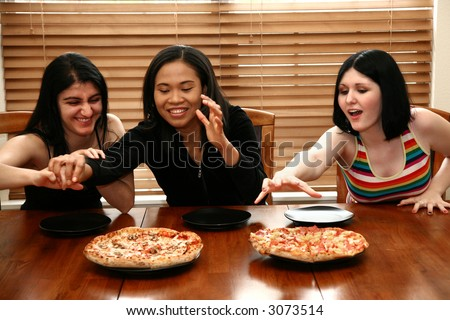 Three college friends sharing pizza for lunch.  Focus on woman in middle. - stock photo