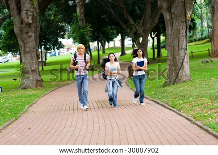 three college students running in campus - stock photo